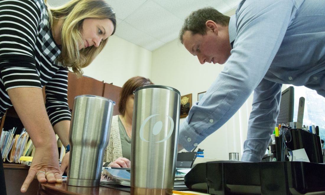 team members working together at a desk with an O'Brien thermos in the center that has the O'Brien O logo