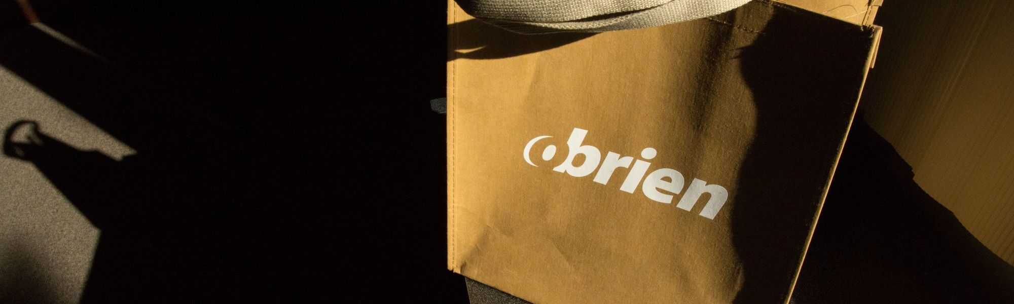 O'Brien tan tote bag with an O'Brien logo in white on the center of the tote bag.