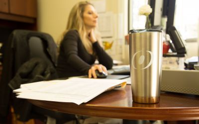 a female O'Brien employee working at her desk with an O'Brien thermos in front of her