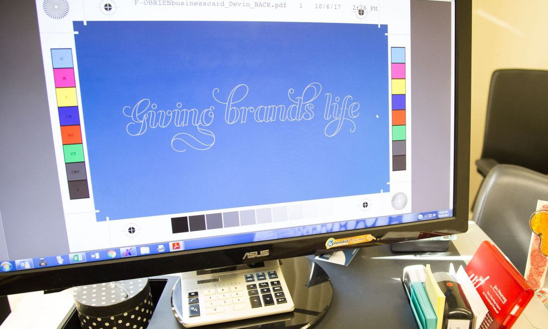 A desktop computer displaying the O'Brien slogan giving brands life on a design editing software.