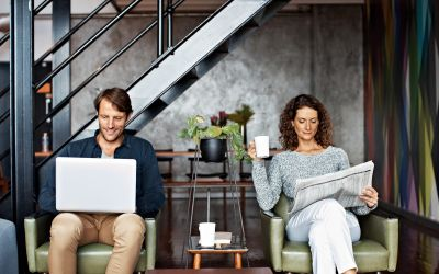 a male reading something on a computer and a female reading the newspaper with a cup of coffee. They are sitting in office waiting room chairs.