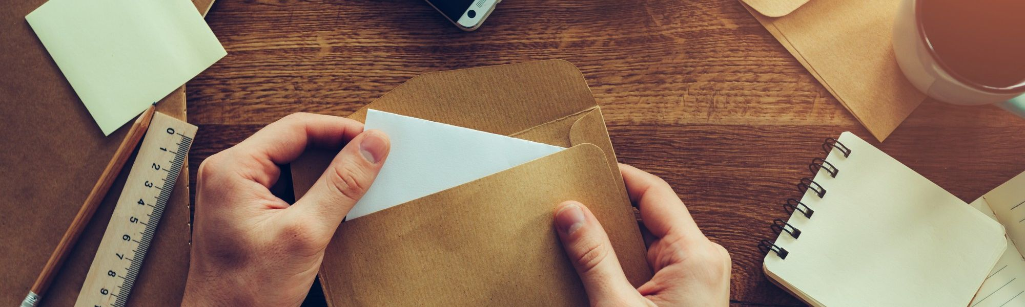 person stuffing an envelope with paper products on a wooden table