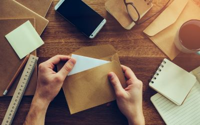 Person stuffing envelopes on a brown table with other papers and envelopes next to it
