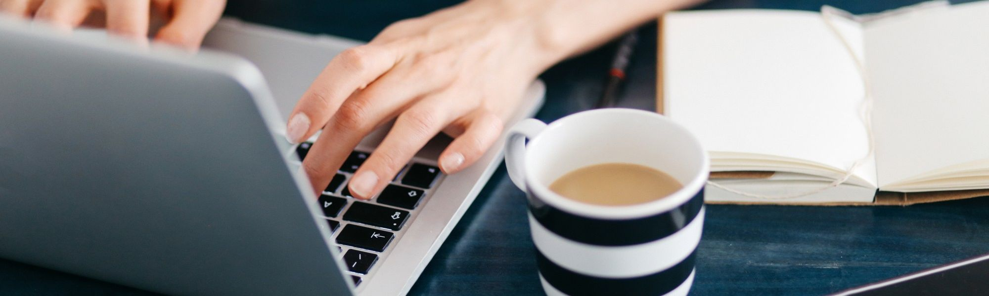 Woman typing on a laptop next to a cup full of coffee