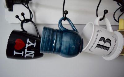 Three mugs hanging on a holder.